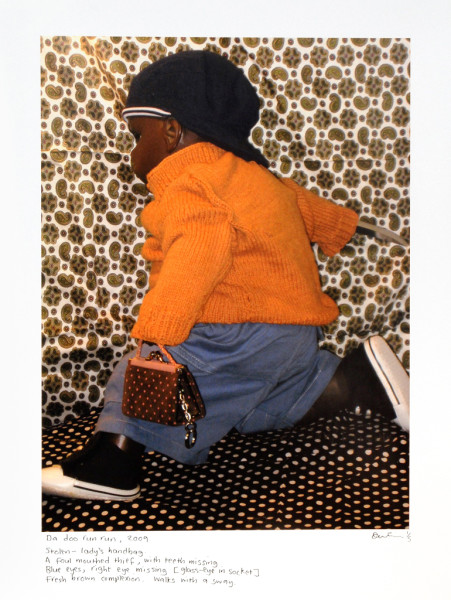 Destiny Deacon Da doo run run, 2009; 'Stolen - ladies handbag. A foul mouthed thief, with teeth missing. Blue eyes, right eye missing [glass-eye in socket]. Fresh brown complexion. Walks with a sway.'; inkjet print from digital image on archival paper; 86 x 66 cm; Image size: 60 x 45 cm; Edition of 5 + 2 APs; enquire