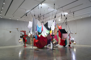 Installation view; Mikala Dwyer Square Cloud Compound, 2010; fabric, stockings, pins, glass bottles, rocks, lights and lamps; Dimensions variable. Adjustable height; enquire