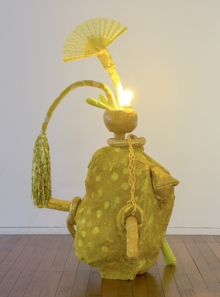 Sarah  Contos Lemon Squeeze, 2015; Glazed earthenware, light globe and fixtures, wood, wire, steel, Bronte beach sand, various fabrics, screen print on linen, upholstery tacks, plastic chain, lighter, plastic fan, found sequinned gloves, ceramic beads, tinsel wig and thread; 137 x 46 x 41 cm; enquire
