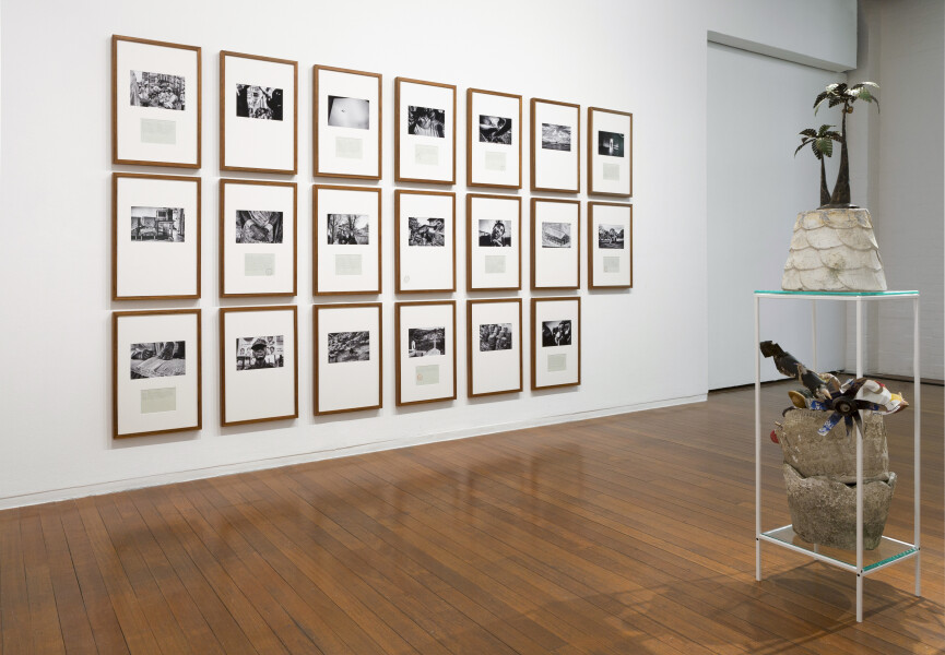 Newell Harry Trade Delivers People (sometimes): Vignettes for N.J., 2017; Two part installation - Part one: twenty framed Lambda prints on Fuji Lustre paper, selected images from artist's archive (2007-2017), hand-typed texts on parchment paper (transcribed from travel journals 2005-17), artist's stamp; Part two: vessel of pulped Port Vila Daily Post newspapers (collected 1999-2011), concrete pot planters, various found/made/collected/gifted artifacts, pencil, artist's stamp, artist designed acrylic and steel structure; Part one: 65cm x 45cm (framed/each); Part two: 169cm x 35 cm x 35cm; enquire